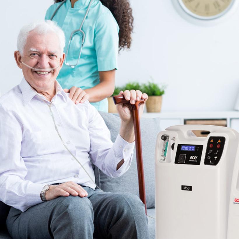 Elderly gentleman using oxygen concentrator