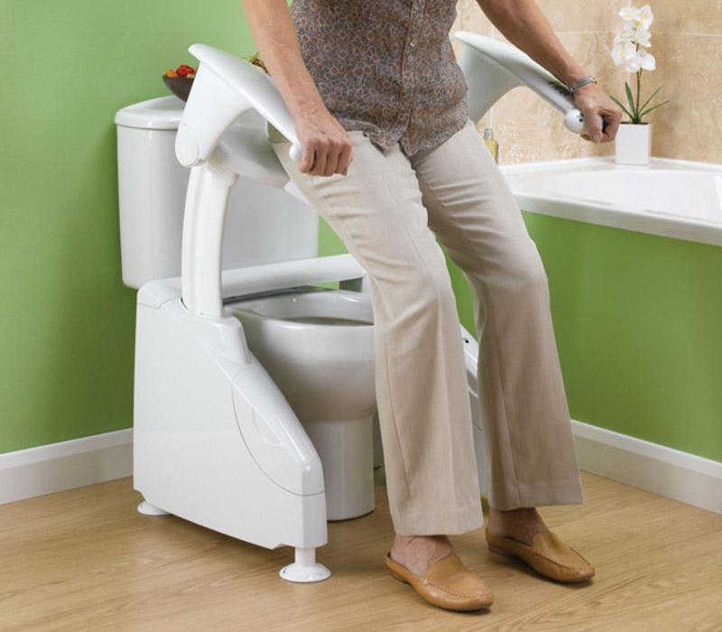 Solo toilet lift in use in bathroom by elderly lady